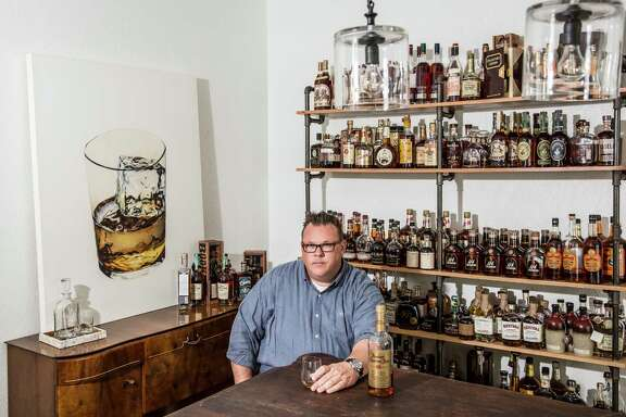 Chris Shepherd at home in Montrose, surrounded by his whiskey collection.