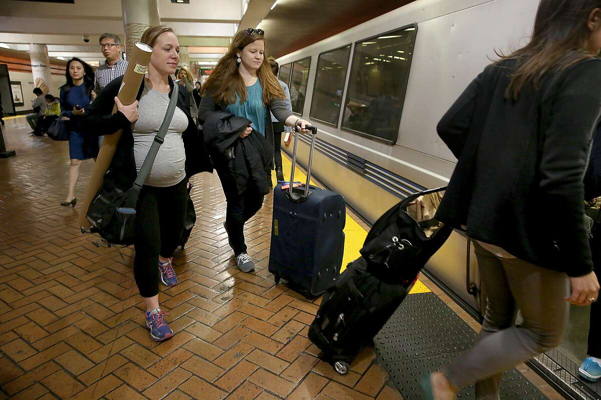 Stephanie Bourque (left), Stephanie Chassen (middle wearing teal shirt), and Jessica Cataldi (right) board a BART train heading for the airport on Tuesday, May 9, 2017, in San Francisco, Calif. Bart has an existing ordinance that makes it illegal for a single passenger to take up more than one seat.