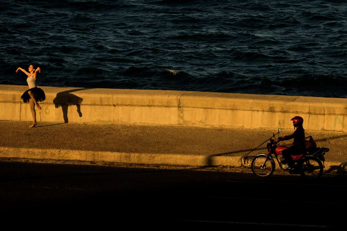 A ballerina poses for photos along Havana's El Malecon at sunset. Once the sun goes down, tourists can continue exploring in the cooler temperatures.