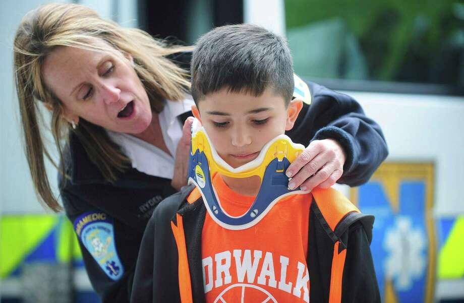 Norwalk Hospital paramedic and EMS supervisor, Lynn Ryder, puts a neck brace on third-grader Dominick Scarpelli as she visits Cranbury Elementary School providing tours of an ambulance and sharing information on EMS and 911 awareness, safety and injury prevention in recognition of National Trauma Awareness Month Tuesday, May 9, in Norwalk. The paramedics and EMTs will be visiting Norwalk schools throughout the month of May. Photo: Erik Trautmann / Hearst Connecticut Media / Norwalk Hour