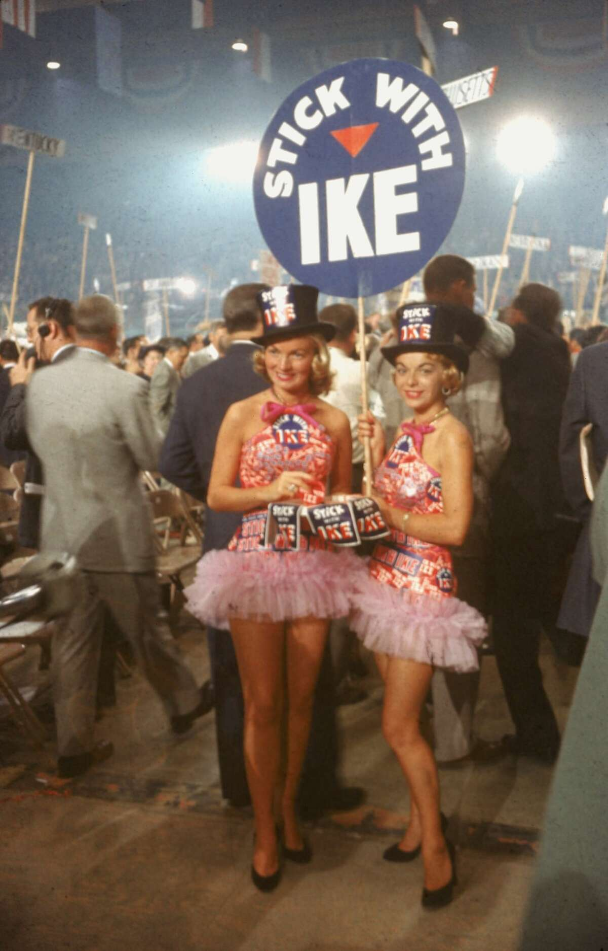 Two young women pose with a placard that reads 'Stick with Ike,' dresses apparently made from Dwight Eisenhower campaign stickers and pink tutus at the Cow Palace for the Republican National Convention. San Francisco hosted the RNC in August 1956.