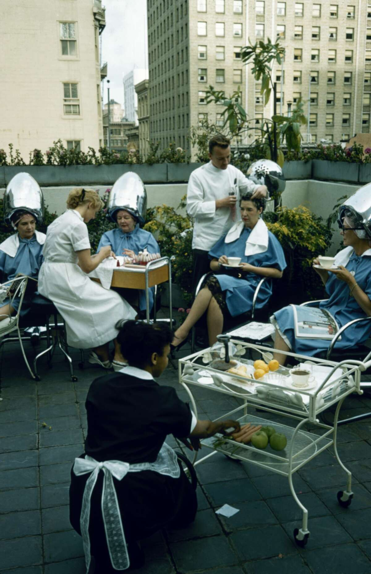 At one of Elizabeth Arden's 1956 spas, women sit under hairdryers, drink tea, or receive manicures in a rooftop garden in San Francisco.
