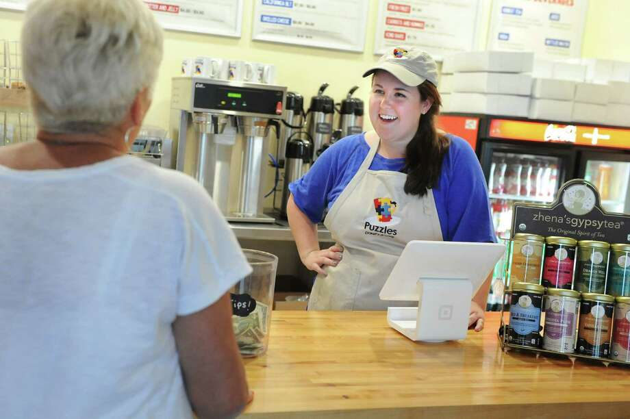 Owner Sara Mae Hickey, right, talks with a customer on Tuesday, June 16, 2015, at Puzzles Bakery and Cafe in Schenectady, N.Y. (Cindy Schultz / Times Union) Photo: Cindy Schultz / 00032293A