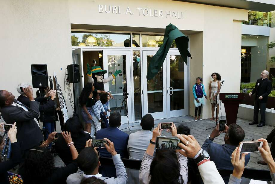 The grandchildren of the late Burl Toler pull down a banner to reveal the new name of the building on the USF campus formerly known as Phelan Hall. Toler — who died in 2009 and would have turned 89 on Tuesday — was a member of the Dons' famed, unbeaten 1951 football team and was a longtime NFL official. Photo: Santiago Mejia, The Chronicle