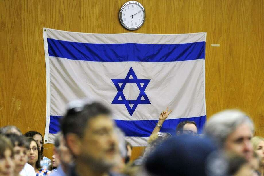 An audience member flashes the peace symbol in front of the Israeli flag during the Fairfield County Rally for Solidarity, Security and Peace at the Jewish Community Center in Stamford, Conn., on Wednesday, July 23, 2014. Photo: Jason Rearick / Jason Rearick / Stamford Advocate