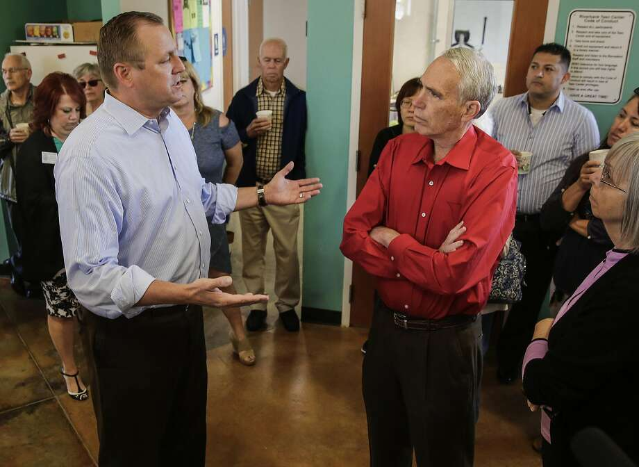 """Denham (left) talks with Al Gelders of Oakdale. The congressman defended his vote as """"something that I thought would help my district."""" Photo: Michael Macor, The Chronicle"""