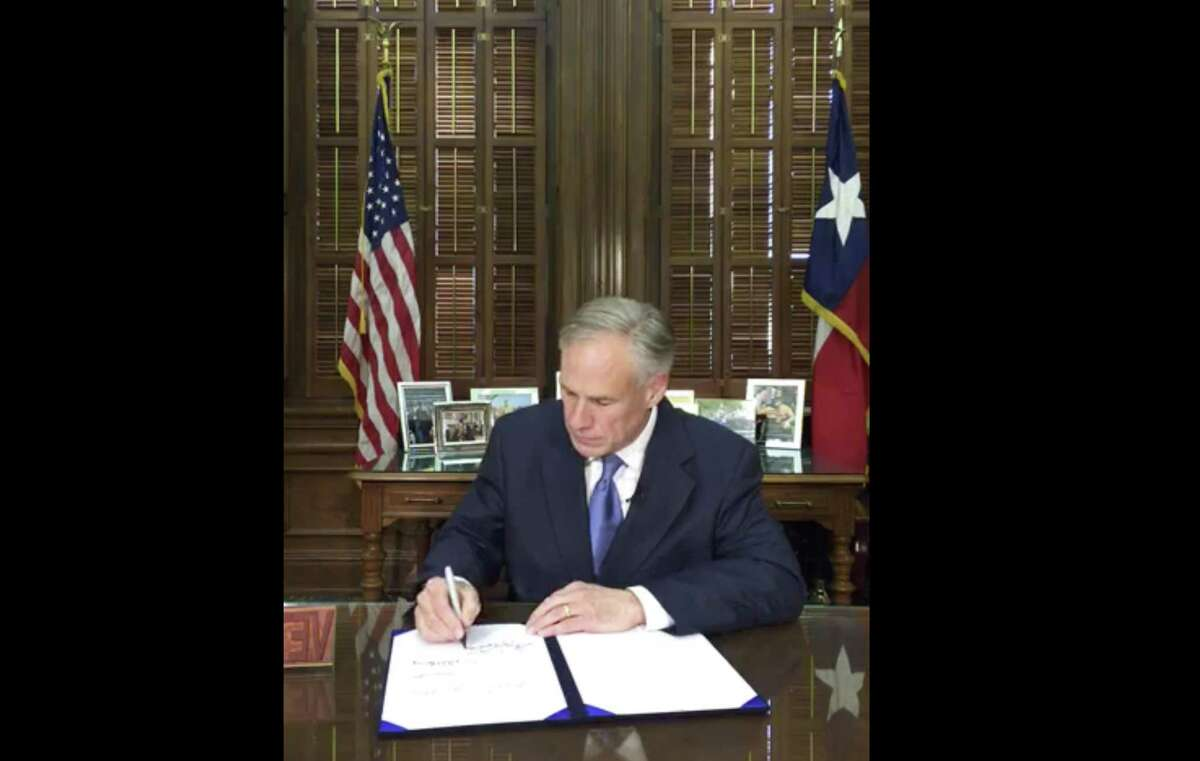 """In this May 7 frame from video posted by the Office of the Governor, Gov. Greg Abbott signs a so-called """"sanctuary cities"""" ban in Austin Texas. The ban lets police ask during routine stops whether someone is in the U.S. legally and threatens sheriffs with jail if they don't cooperate with federal immigration agents."""