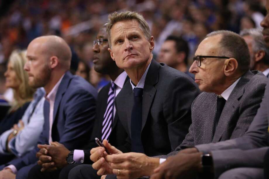 Warriors head coach Steve Kerr, flanked by now-acting head coach Mike Brown (striped tie) and assistant coach Ron Adams, is trying to help Brown without infringing on Brown's ability to run the team. Photo: Christian Petersen / Getty Images / 2016 Getty Images
