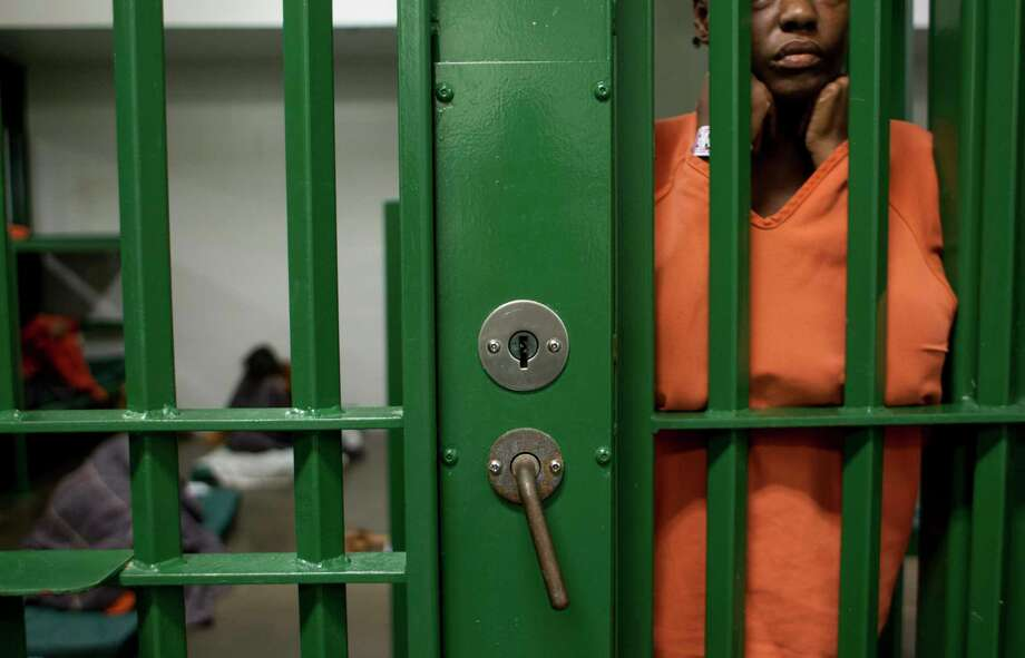 An inmate peers out at activity outside her cell at the Harris County Jail in Houston. (Chronicle File Photo) Photo: Johnny Hanson, Staff / Â 2013  Houston Chronicle