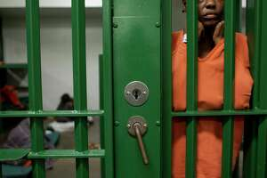 An inmate peers out at activity outside her cell at the Harris County Jail in Houston. (Chronicle File Photo)