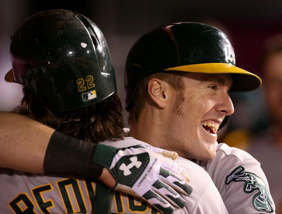 ANAHEIM, CA - JUNE 12:  Josh Reddick #22 (L) and Mark Canha #20 of the Oakland Athletics celebrate n the dugout after both score on Reddick's two run home run in the seventh inning against the Los Angeles Angels of Anaheim at Angel Stadium of Anaheim on June 12, 2015 in Anaheim, California.  (Photo by Stephen Dunn/Getty Images) Photo: Stephen Dunn, Getty Images