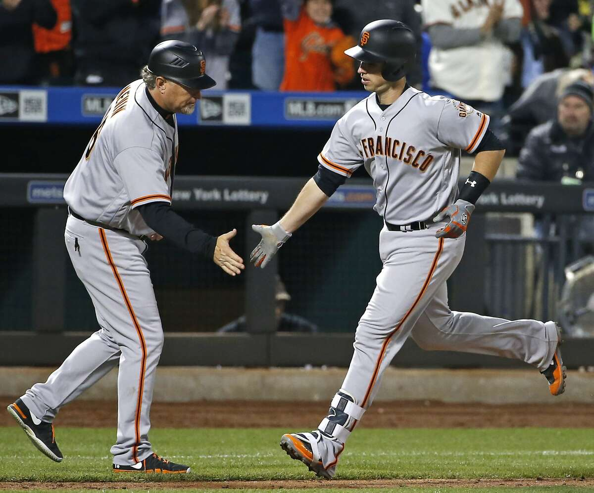 San Francisco Giants third base coach Phil Nevin, left, greets San Francisco Giants' Buster Posey after Posey hit a solo home run during the fourth inning of the team's baseball game against the New York Mets, Tuesday, May 9, 2017, in New York. (AP Photo/Kathy Willens)