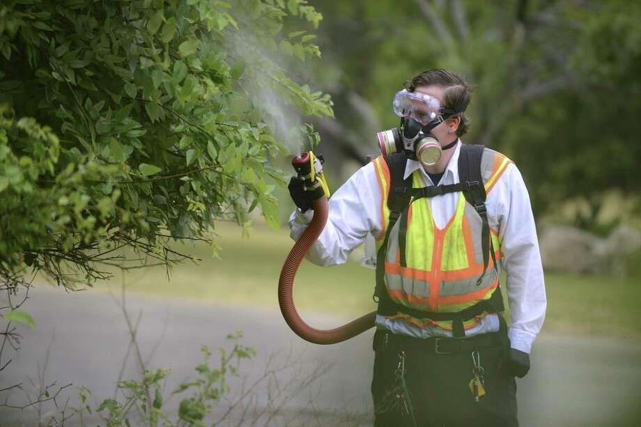 Benjamin Buvia uses a backpack mister/sprayer for mosquito control at Lady Bird Johnson Park on Tuesday, May 9, 2017. Photo: Billy Calzada /San Antonio Express-News / San Antonio Express-News