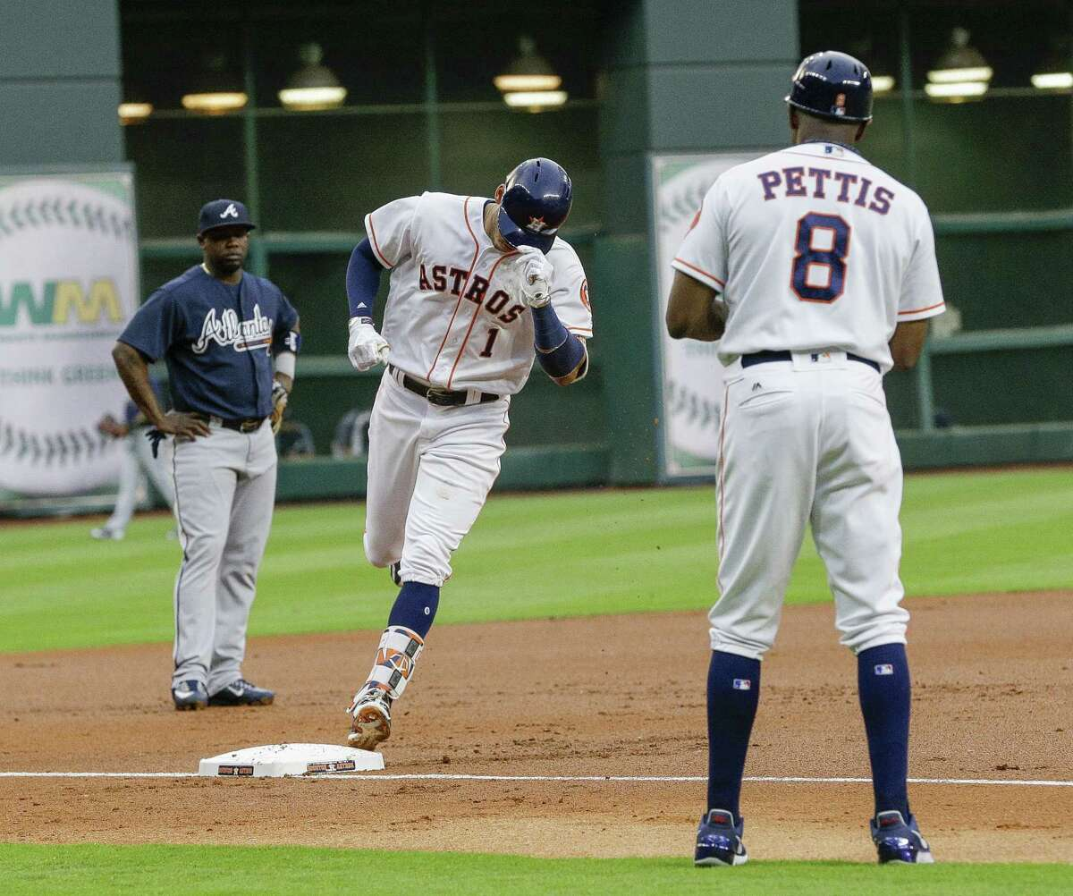 HOUSTON, TX - MAY 09: Shortstop Carlos Correa #1 of the Houston Astros rounds third base in front of third base coach Gary Pettis #8 after hitting a three-run home run in the first inning against the Atlanta Braves at Minute Maid Park on May 9, 2017 in Houston, Texas.