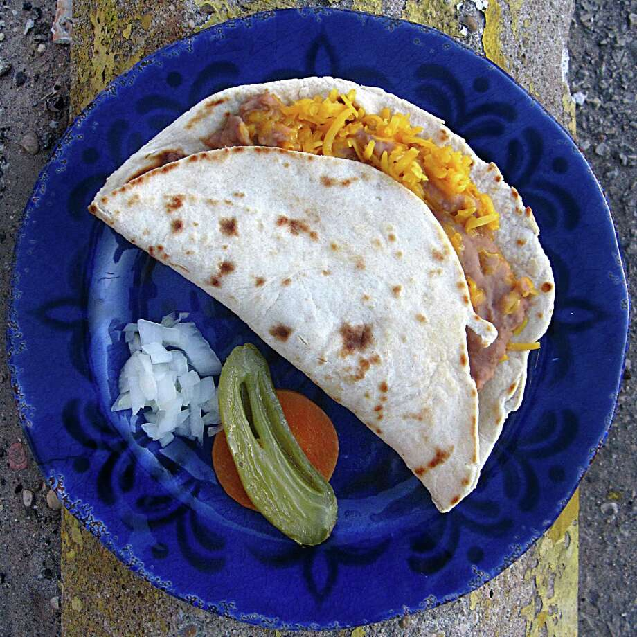 Bean and cheese taco with escabeche and onions on a handmade flour tortilla from Taquería San Juan #1. Photo: Mike Sutter /San Antonio Express-News
