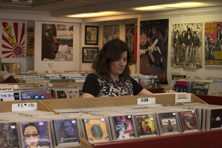 Left: Regular customer Jessica Ascencio, a local, looks for classic rock records at Red Devil Records in San Rafael. Photo: Erik Castro, Special To The Chronicle
