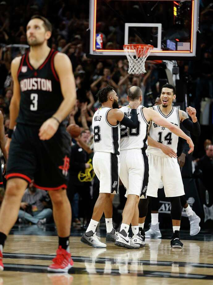 The Rockets' Ryan Anderson, left, solemnly walks off the floor. Across the court, teammates congratulate Manu Ginobili on his defensive heroics following the Spurs' 110-107 overtime victory Tuesday night. Photo: Karen Warren, Staff Photographer / 2017 Houston Chronicle