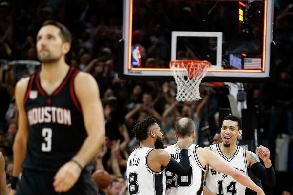 The Rockets' Ryan Anderson, left, solemnly walks off the floor. Across the court, teammates congratulate Manu Ginobili on his defensive heroics following the Spurs' 110-107 overtime victory Tuesday night.