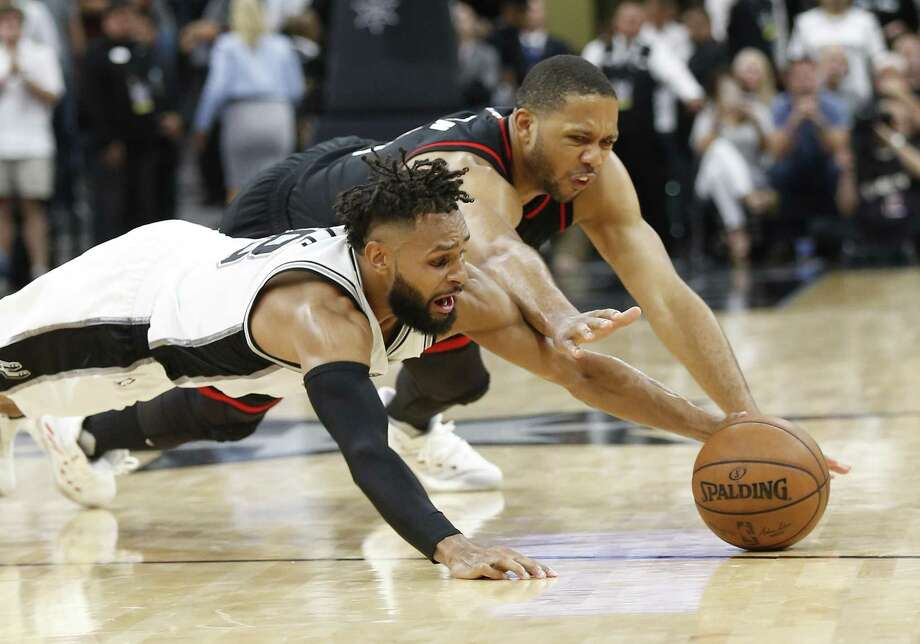 Spurs' Patty Mills and the Rockets' Eric Gordon dive for a loose ball in the closing moments of overtime of Game 5 at the AT&T Center on May 9, 2017. Spurs defeated the Rockets 110-107. Photo: Kin Man Hui /San Antonio Express-News / ©2017 San Antonio Express-News