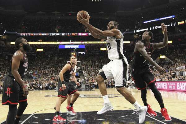 Spurs' Kawhi Leonard (2) drives on Houston Rockets' James Harden (13), Ryan Anderson (3) and Patrick Beverley (2) in Game 5 of the Western Conference semifinals at the AT&T Center on May 9.