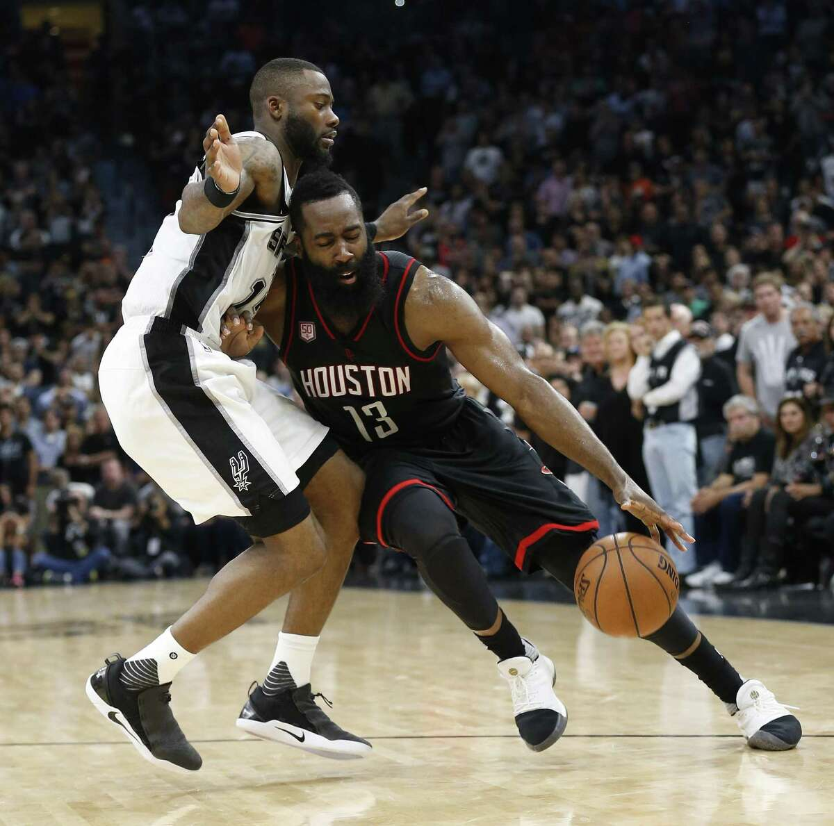 Spurs' Jonathon Simmons draws a charging fould against the Rockets' James Harden during Game 5 at the AT&T Center on May 9, 2017.