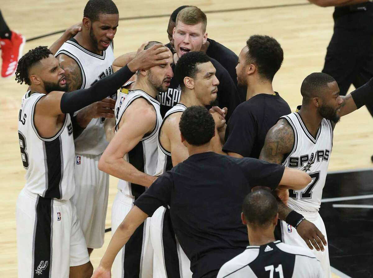Teammates gather around the Spurs' Manu Ginobili after he blocked Houston Rockets' James Harden to end overtime in game five of the Western Conference semifinals at the AT&T Center on May 9, 2017. The Spurs won in overtime 110-107 to go up in the series, 3-2.