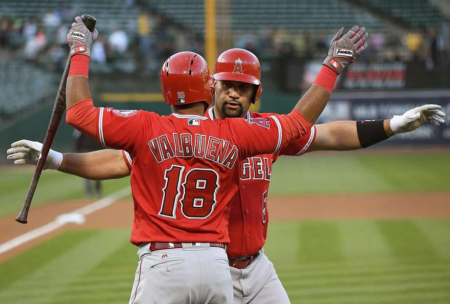 Luis Valbuena greets Albert Pujols at home plate after the Angels' first baseman hit the 596th home run of his career. Photo: Thearon W. Henderson, Getty Images