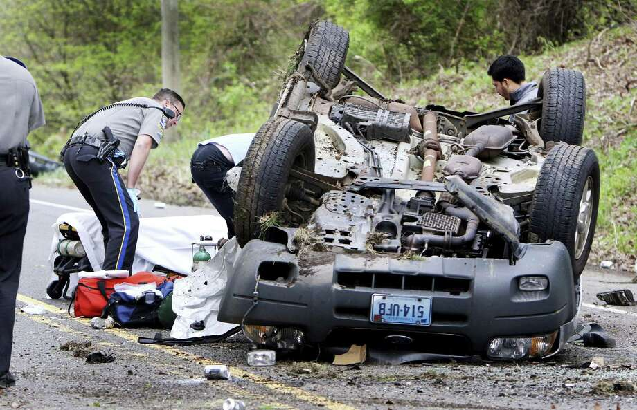 In this May 9, 2017 photo, medics pull a victim from an over turned vehicle in Woodbury, Conn. A second vehicle landed in a nearby stream. Katherine Ann Berman, wife of longtime ESPN broadcaster Chris Berman died in the traffic crash. Photo: Steven Valenti /Republican-American Via AP / Republican-American