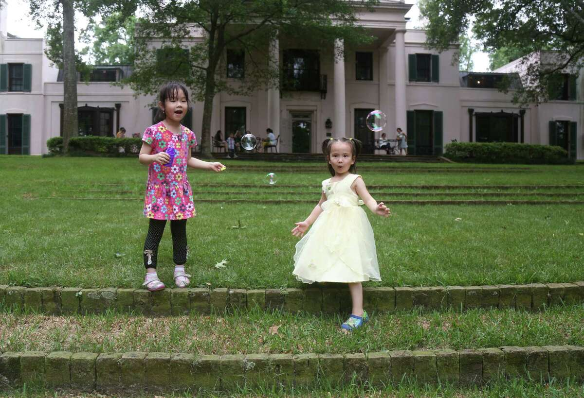 Anna Richmond, 4, tries to pop bubbles with her friend Tracy Zhou as their mothers watch from the porch at the Bayou Bend Gardens Sunday, May 10, 2015, in Houston. ( Jon Shapley / Houston Chronicle )
