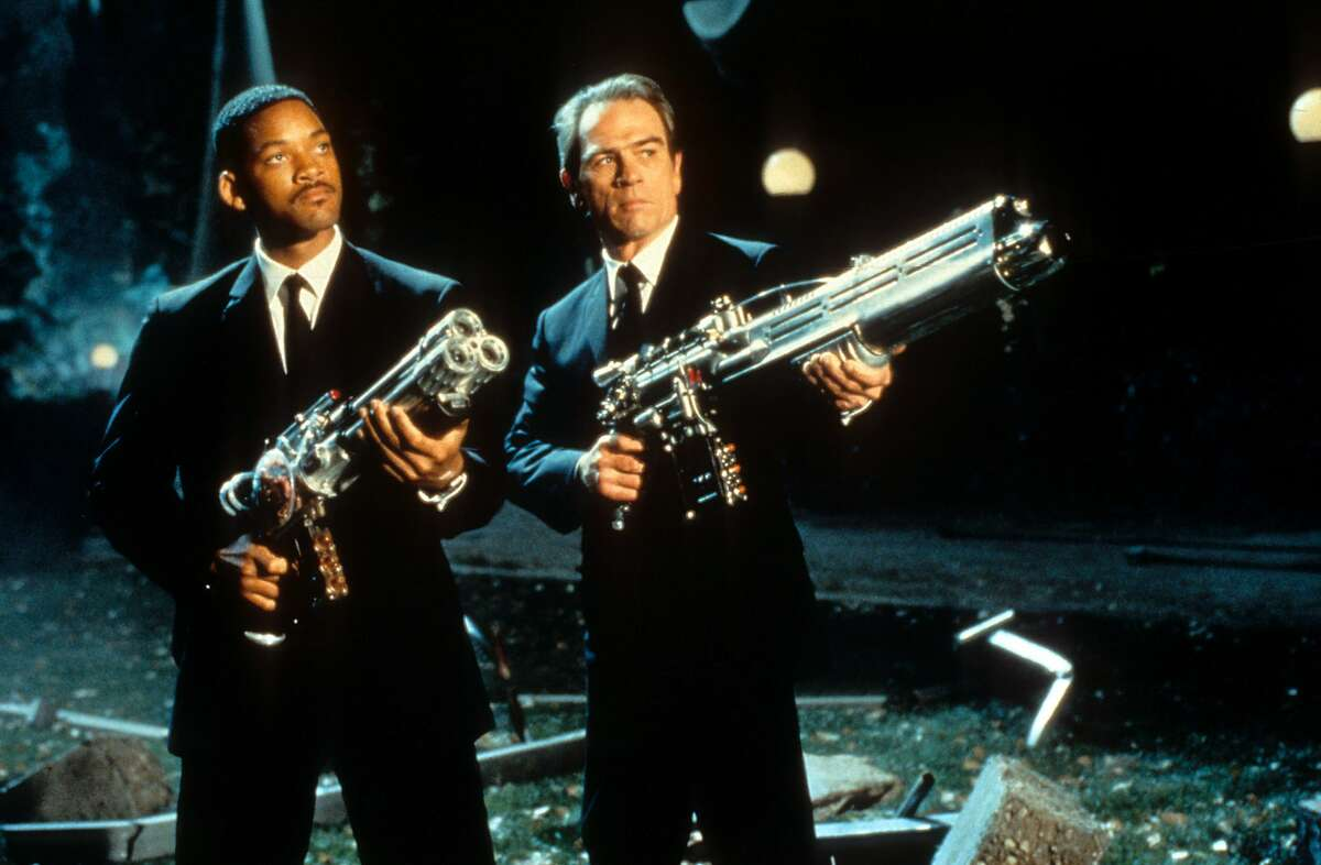 Will Smith and Tommy Lee Jones aiming their weapons towards the sky in a scene from the film 'Men In Black', 1997. (Photo by Columbia Pictures/Getty Images)
