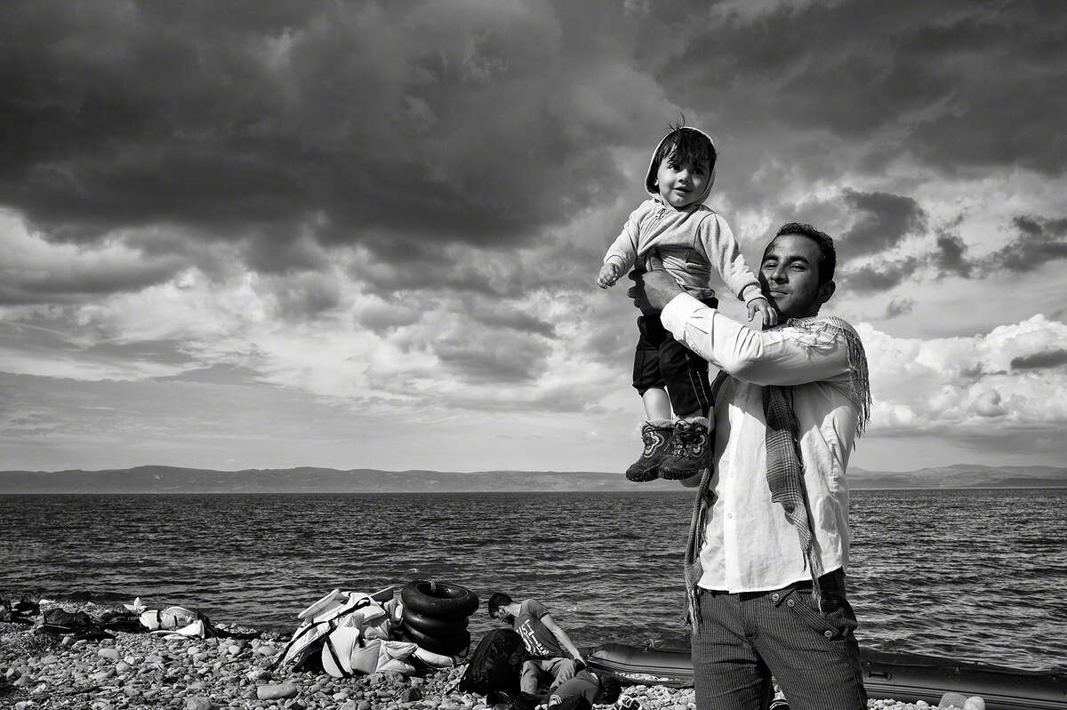 Tom Stoddart, Lesbos, Greece, 2015: A father celebrates his family's safe passage to Lesbos after a stormy crossing over the Aegean Sea from Turkey.