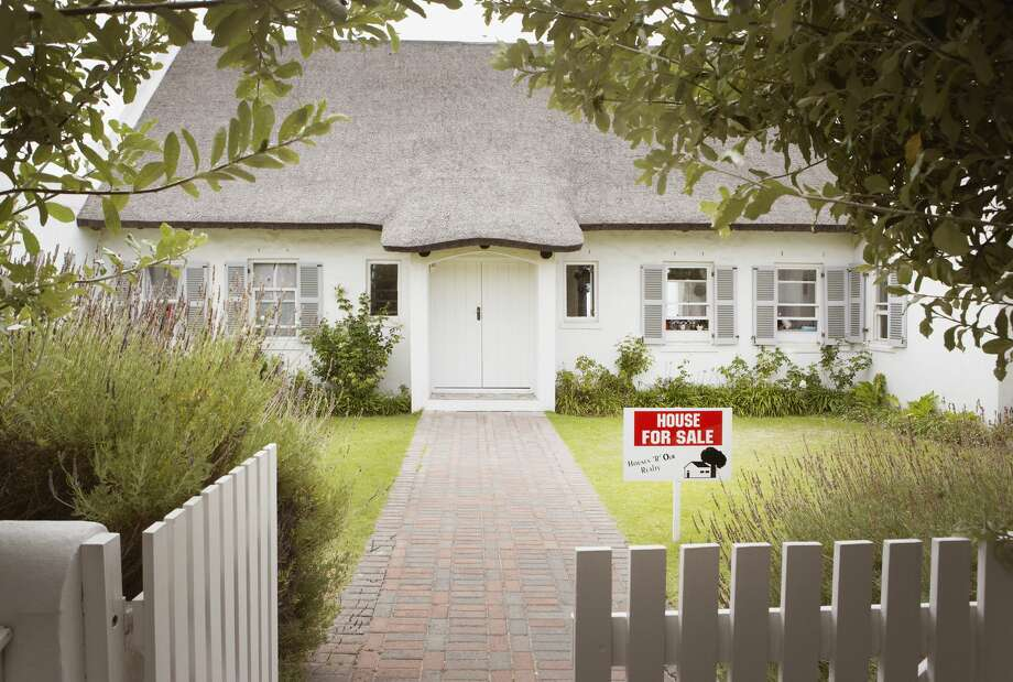 House with for sale sign in yard and open wooden fence Photo: Tom Merton/Getty Images