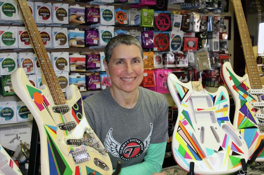 Julie Rosenberg, with her painted guitars at New Canaan Music on May 4. Photo: Justin Papp / Hearst Connecticut Media / New Canaan News