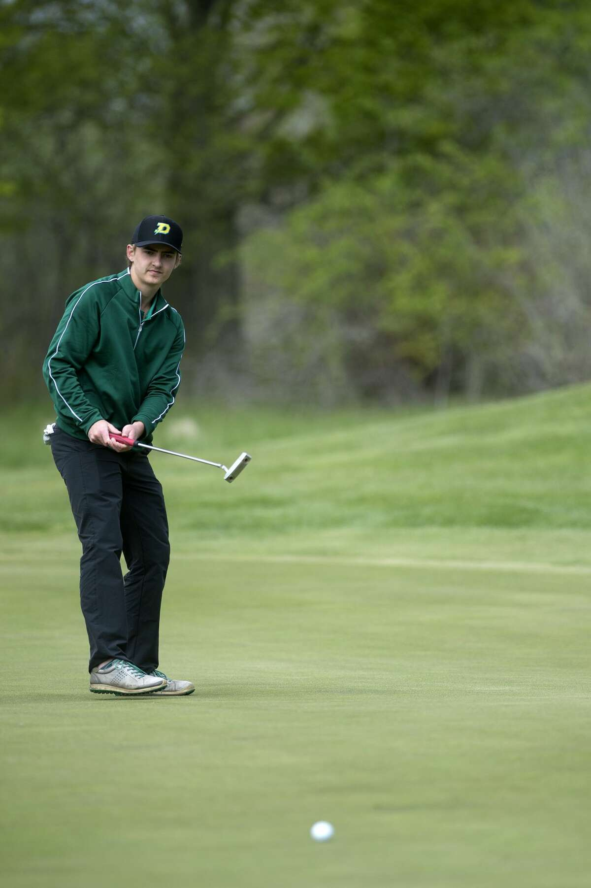 Dow High's Joey Johnson watches his putt on the seventeenth hole during the Wednesday Saginaw Valley League golf jamboree at Currie Golf Course.
