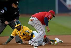 OAKLAND, CA - MAY 09:  Rajai Davis #11 of the Oakland Athletics steals third base sliding under the tag of Yunel Escobar #0 of the Los Angeles Angels of Anaheim in the bottom of the first inning at Oakland Alameda Coliseum on May 9, 2017 in Oakland, California.  (Photo by Thearon W. Henderson/Getty Images)