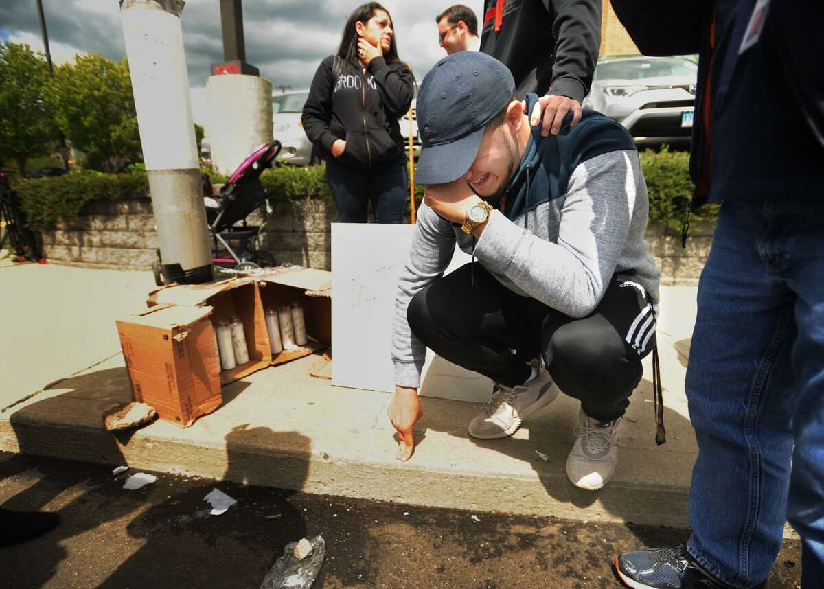 Isaiah Delgado, of Bridgeport, breaks down as he visits the site where his cousin, Jayson Negron, 16, of Bridgeport, was shot and killed following an altercation with police on Fairfield Avenue in Bridgeport on Tuesday. The shooting is being investigated by the State Police.