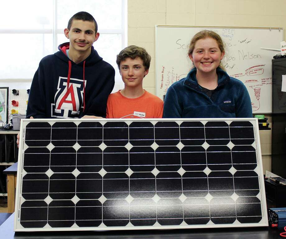John Renda, left, Shea Smith and Megan Rigione with one of the solar panels that will be installed at New Canaan High School thanks to their efforts. Photo: Erin Kayata / Hearst Connecticut Media / New Canaan News