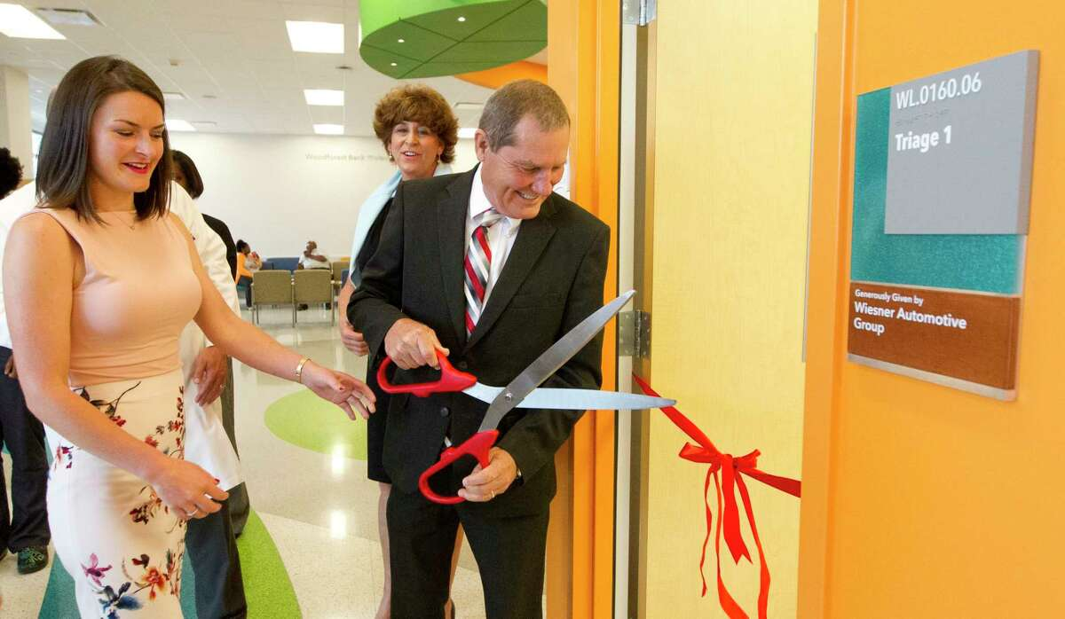 Don Wiesner, center, officially opens an emergency room triage room donated by the Wiesner family as his daughter Falon Wiesner-Jones looks on at Texas Children's Hospital The Woodlands, Wednesday, May 10, 2017, in Conroe.