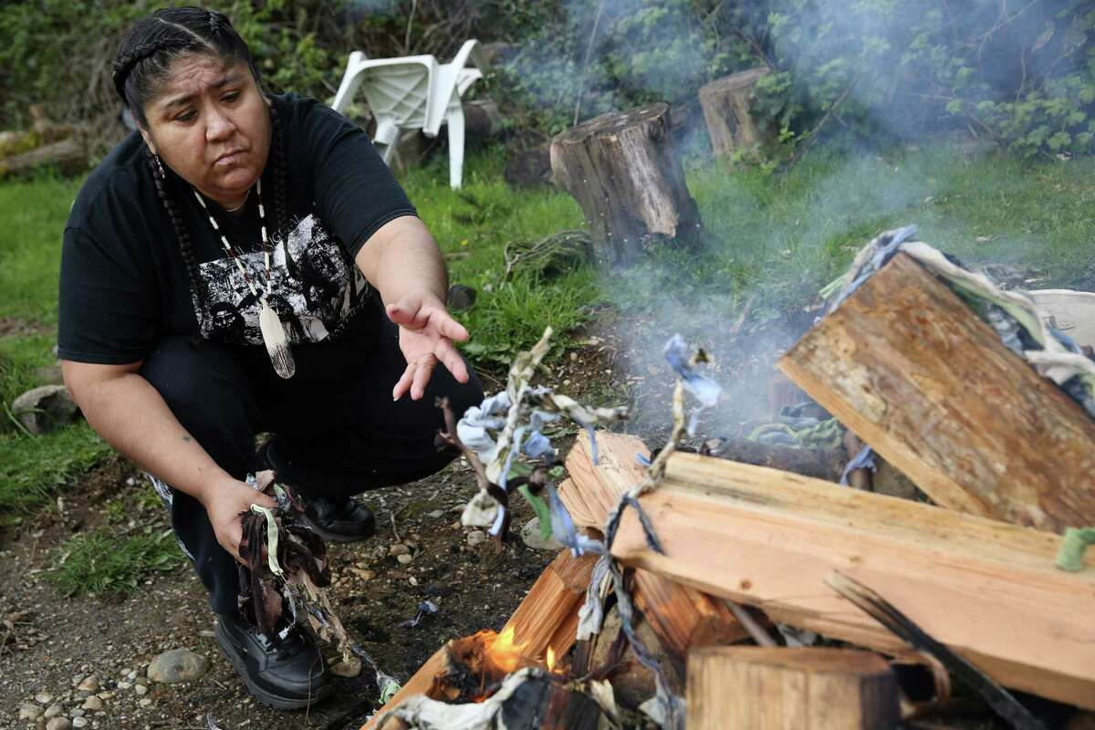 Bridgette burns cloth ties that held the old sweat lodge together as she and other women build a new lodge for an evening sweat with other members of Mother Nation, a non-profit that aids native women who are survivors of domestic violence, abuse and addiction, April 11, 2017.