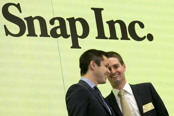 FILE - In this Thursday, March 2, 2017, file photo, Snapchat co-founders Bobby Murphy, left, and CEO Evan Spiegel ring the opening bell at the New York Stock Exchange as the company celebrates its IPO. Since it couldn't buy its smaller rival, Facebook is bent on copying Snap to death. Snap Inc., the company behind Snapchat, meanwhile, is intent on forging ahead against its much bigger rival, courting older users, keeping young ones and along with them, advertisers. (AP Photo/Richard Drew, File)