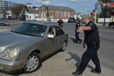 Norwalk Police Officers direct a car out of traffic on West Ave as Officer Jamile Wright points the driver into a parking lot and will issue her a ticket for distracted driving  in 2015 in Norwalk, Conn.
