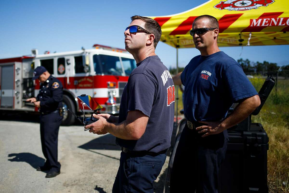Kevin White, center, pilots the drone as Chris Dennebaum of the Menlo Park Fire Protection District watches the livestream camera in a flight test during a search and rescue training at SLAC National Accelerator Laboratory in Menlo Park, Calif. Friday, May 5, 2017.