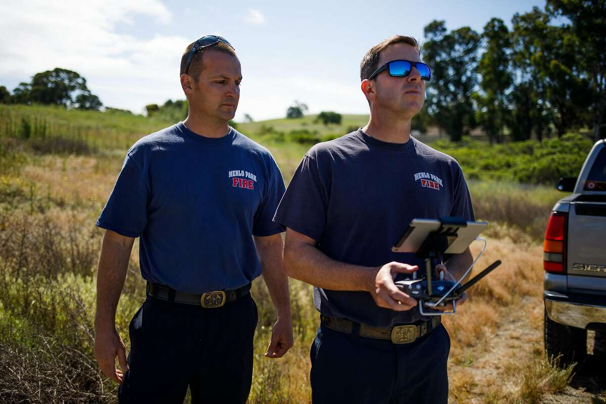 From the left, Chris Dennebaum watches Kevin White of the Menlo Park Fire Protection District instruction in a flight test during a search and rescue training at SLAC National Accelerator Laboratory in Menlo Park, Calif. Friday, May 5, 2017.