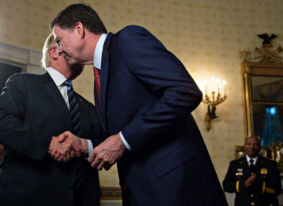 U.S. President Donald Trump (L) shakes hands with James Comey, director of the Federal Bureau of Investigation (FBI), during an Inaugural Law Enforcement Officers and First Responders Reception in the Blue Room of the White House on January 22, 2017 in Washington, DC.  Photo: Pool / Getty Images 2017