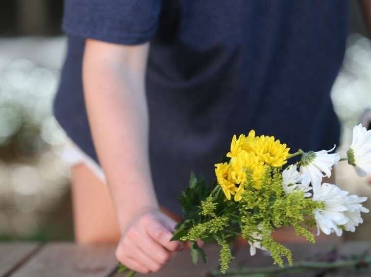 Students led by Montana Moore place flowers on the benches outside a University of Texas at Austin gym Tuesday May 2, 2017, as the campus tries for normalcy the day after a biology student knifed fellow students (Ralph Barrera, Austin American-Statesman).