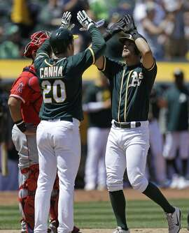Oakland Athletics' Chad Pinder, right, celebrates with Mark Canha (20) after hitting a two run home run off Los Angeles Angels' Jesse Chavez in the fifth inning of a baseball game Wednesday, May 10, 2017, in Oakland, Calif. (AP Photo/Ben Margot)