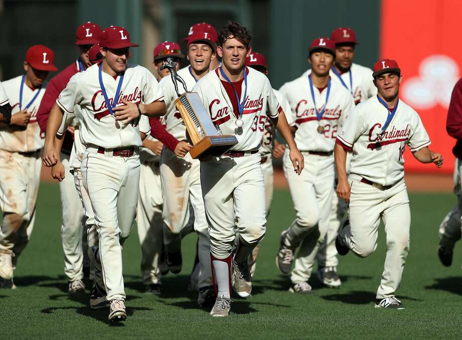 Lowell pitcher Joe Solomon (with trophy) leads a victory lap at AT&T Park as the Cardinals celebrate their 2-0 win over Washington in the San Francisco Section championship game. Photo: Scott Strazzante, The Chronicle
