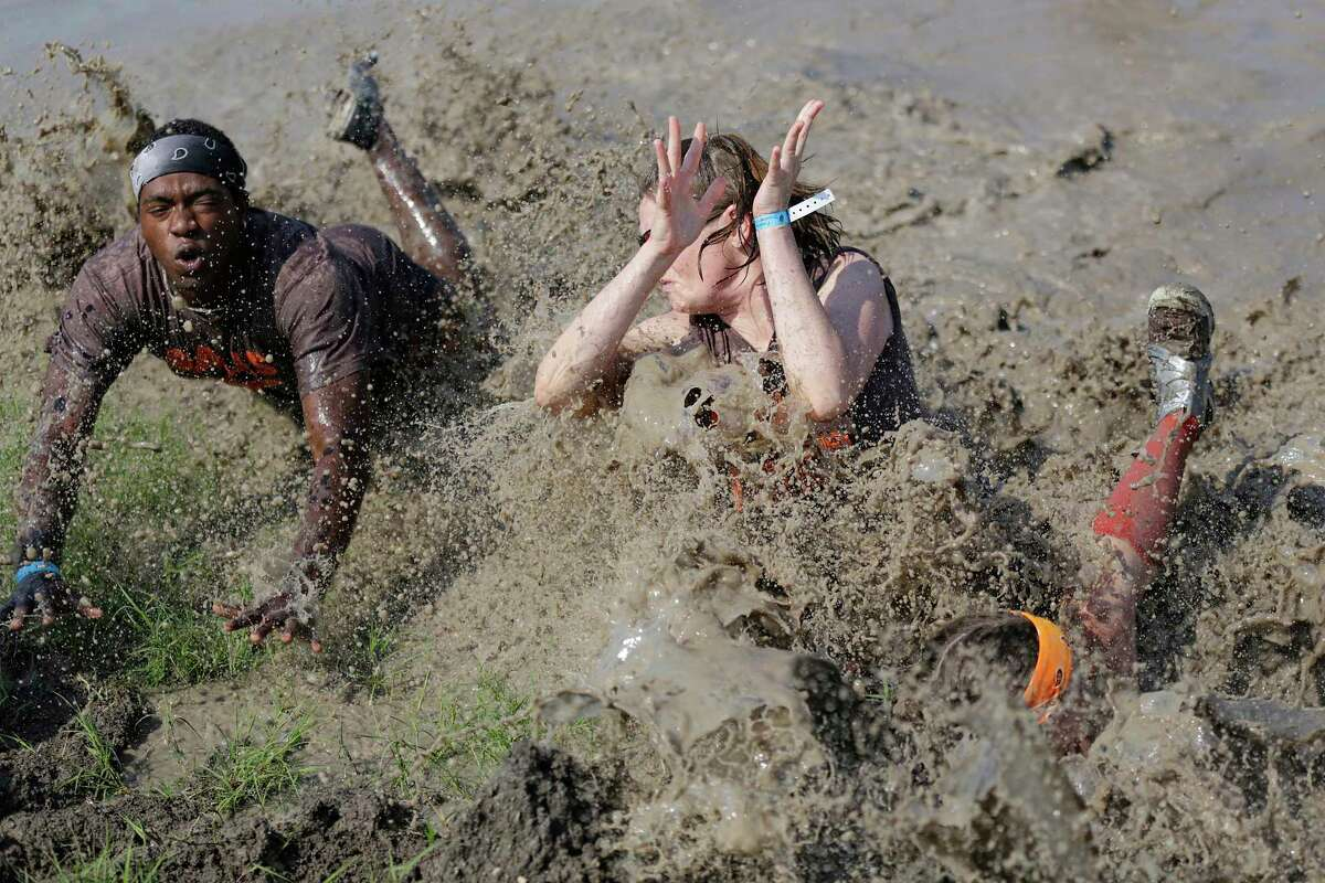 Raymond Henderson, left, Alison Schwalenberg, and Kelsey Oakley miss the volleyball but find a mouthful of muck during a previous mud volleyball tournament at the Pasadena Strawberry Festival.