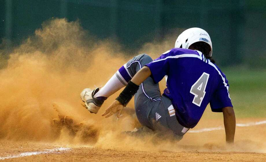 Lily Atkinson #4 of Willis slides into second after beating the throw to Bryan third baseman Rachel Agnello (8) during the fourth inning in Game 1 of a Region III-5A quarterfinal series Wednesday, May 10, 2017, in Montgomery. Photo: Jason Fochtman, Staff Photographer / © 2017 Houston Chronicle