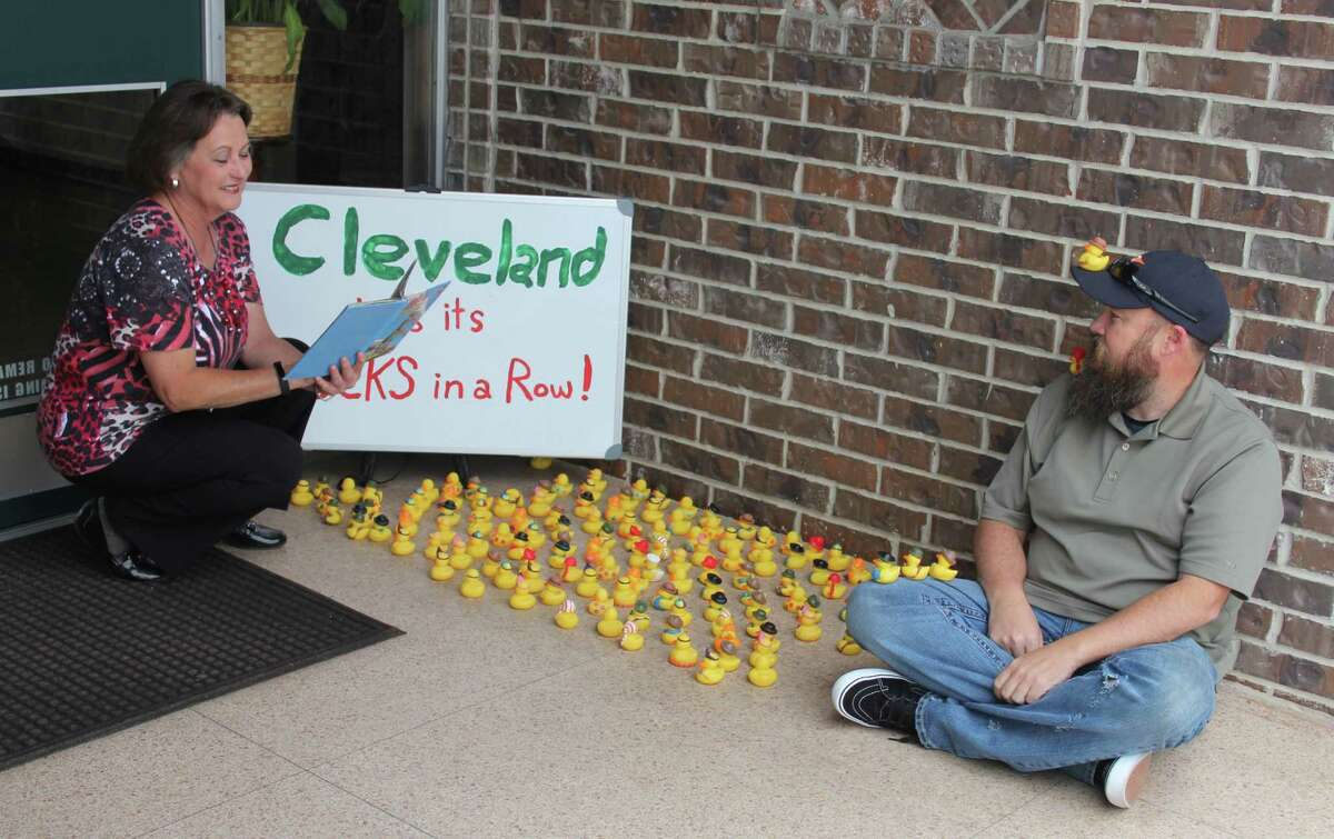 Sherry Cook, at the insistence of her tenant, attorney Donny Haltom, good-naturedly poses for a fun photo of her reading a book to a group of rubber ducks and Haltom.